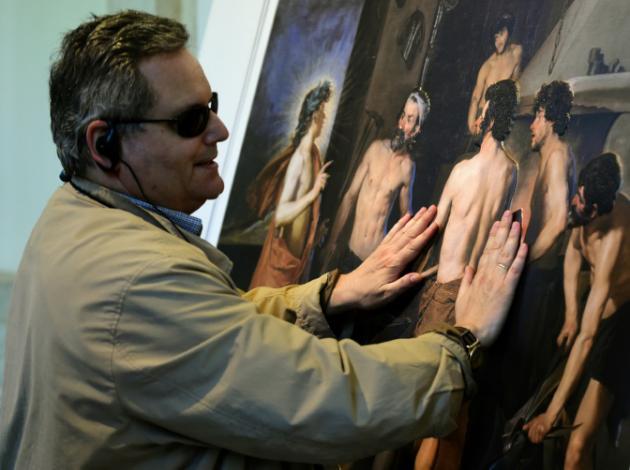 AFP/AFP - José Pedro González, visitante ciego del Museo del Prado de 56 años, toca una reproducción de 'La fragua de Vulcano', uno de los cuadros más famosos de Diego Velázquez, en Madrid el 18 de junio de 2015
